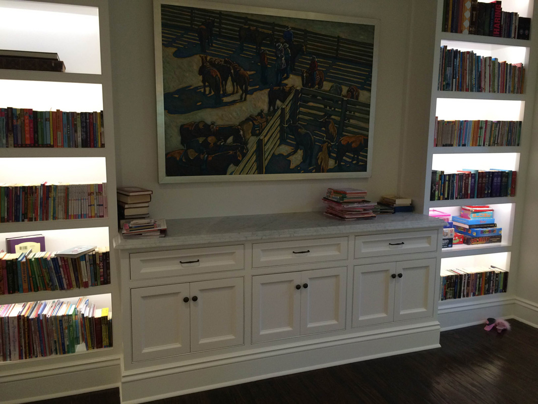 Custom bookcase with lights on shelves holmby Residence